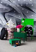 Green-painted trunks on four legs and patterned storage drums against wallpapered wall