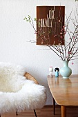Chair with white animal skin next to a 50's style wooden table and flower vase in front of a wall with a poster hanging on it