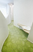 Curved bathroom installations and green, retro floor tiles