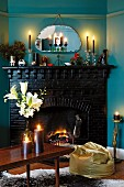 Romantic, candlelit atmosphere with golden beanbag and dark-painted brick fireplace combined with blue-painted walls