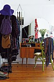 Retro dressing table, bright green wicker chair and open clothes rack in bedroom