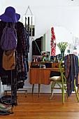 Retro-Schminktisch mit knallgrünem Korbstuhl und offener Kleiderständer im Schlafzimmer