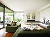Moderne grüne Sofagarnitur mit drapierten Kissen in grosszügigem Wohnraum und Blick in Patio