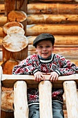 Young boy leaning on a wooden railing in front of a log cabin