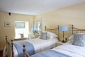 Cream bedroom with pale blue accessories combined with chrome country-house twin beds