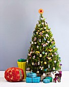 Red pouffe, wrapped presents and animal ornaments under Christmas tree decorated with many different figurines