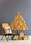 Christmas presents below stylised Christmas tree made from paper triangles with paper Christmas decorations on grey wall