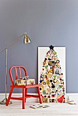 Stylised Christmas tree collage on white plywood panel; wrapped present on red wooden chair and industrial-style standard lamp