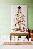 Christmas tree decorations arranged in shape of Christmas tree on white panel above presents and paper bags used as tealight holders