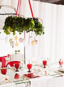 Wreath decorated with Christmas baubles suspended from ceiling above set table with red, retro wine glasses