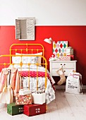 Parcels on white wooden floor next to single bed with yellow-painted metal frame and bedside table against wall with red, painted dado