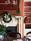 Prunkvoller, offener Kamin mit darüberhängendem, goldgerahmten Spiegel und Weihnachtsdekoration