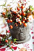 Late-summer bouquet with rosehips, roses and branches of spirea
