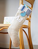 Modern Christmas stocking hanging from back of wooden chair