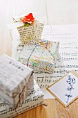 Presents wrapped imaginatively in pages of books, sheet music and old street maps