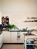 Many items of crockery on wall-mounted shelves and in shelving unit flanking aphorism in relief on kitchen wall