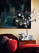Small tree decorated with Christmas decorations and presents in front of dark painting in living room