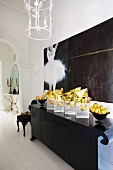Gold Christmas decorations on black postmodern sideboard and modern painting of ballerina in elegant entrance hall