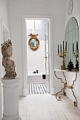 Gilt accents and antique accessories in hallway with view into bathroom through open door