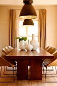 White ceramic vases on solid wood dining table below large ceiling lamps in front of dining room window