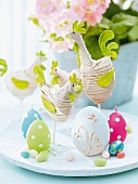 Easter decoration - fabric hens, egg-shaped candles and chocolate eggs on white platter