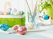 Painted Easter eggs in front of basket of eggs and paintbrushes in glass of water
