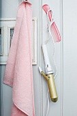 Pink towel and retro curling iron hanging from hooks on white wooden wall