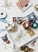 Weisses Tablett mit Weihnachtsschmuck und verschiedene Weihnachtsdeko-Artikeln auf weisser Ablage
