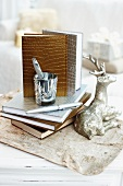 Note books with gold and silver mock-croc bindings next to silver reindeer ornament and writing utensils on vintage paper