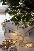 Perlen- und Lichterketten vor und auf Weihnachtsbaum