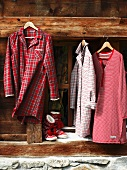 Old-fashioned night attire hanging from wooden beam on coat hangers