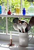Assorted Kitchen Utensils in a Crock by a Window; Glass Bottles on the Windowsill