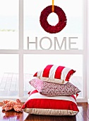 Festive wreath made from red feather boa in window above pile of scatter cushions