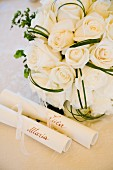 White bridal bouquet behind scrolls of paper bearing names of bride and groom