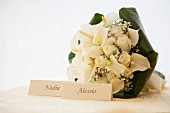 Bridal bouquet with roses and calla lilies behind cards bearing names of bride and groom