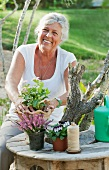 Middle aged woman arranging flowers at a garden table