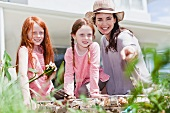 Mother and daughters gardening