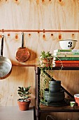 Open shelf made of rusty metal against wooden wall with hanging cookware
