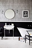 Washstand with chrome frame and bathtub in front of partially black-tinted wall, papered above with a gray pattern