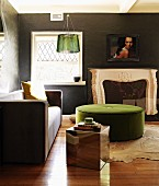 Slate-effect walls in interior with designer sofa, green ottoman and mirrored cubic table