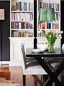 Lustrous green designer lamp above modern, black and white dining set; bookcases in background against dark wall