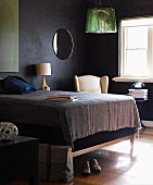 Double bed with tall, upholstered frame in small bedroom with black walls