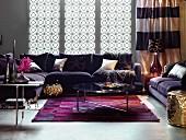 Glamouröses Wohnzimmer mit violetter Polstergarnitur, Teppich und goldfarbenem Sitzpouf