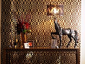 Artistic table lamp and horse ornament on metal console table against ornately patterned wallpaper