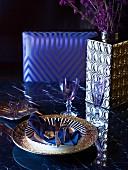 Gedeck mit Goldrandteller, Gläsern, silberglänzender Vase auf Esstisch, Stuhl mit eleganter Polsterlehne