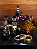 Various elegant perfume bottles, bowl of orchid flowers and bracelets on black dressing table