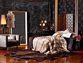 Fur blankets, exotic-wood parquet floor, large mirror leaning against wall and elegant fabrics in bedroom
