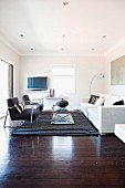Armchairs with metal frames and black upholstery and coffee table opposite white sofa on rug in traditional living room with dark wooden floor