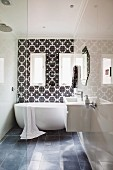 Modern bathroom with floating washstand on glossy wall and free-standing bathtub against wall with black and white tiled wall with Oriental pattern
