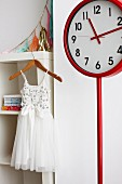 White tulle dress on wooden clothes hanger and red station clock in girl's bedroom
